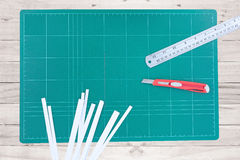 A ruler and cutter on green cutting mat Stock Image