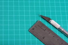 Ruler knife on a green cutting mat Stock Image
