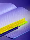 Ruler and pencil. Ruler and dark blue pencil on a background of the open writing-book, covered by cold light Royalty Free Stock Photography