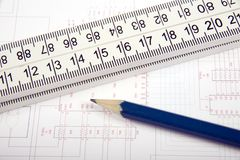 A ruler and pencil. A pencil on a ruler, over the top of some plans Royalty Free Stock Photography