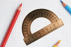 Ruler protractor and pencils on a notebook sheet stock photography