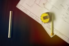 Black table, floor plan, ruler, pencil, measuring tape stock photos