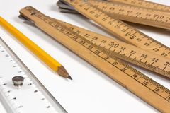 Rulers and Pencil on White Background. A measuring stick, a ruler and a pencil on a white background Stock Photo