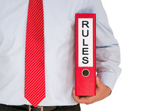 Rules. Text 'rules' in black uppercase letters on white label fixed to a red binder held under the arm of a businessman wearing a pale blue shirt and red striped Stock Photos