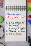 Rules to Live a Happier Life. Written in notebook on wooden desk with marker pen and glasses. Top view Royalty Free Stock Photography