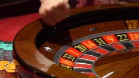 Ruleta del casino en el movimiento, la bola de la rueda de hilado y la mano del crupié metrajes