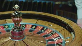 Ruletowego ko?a i krupiera r?ka z bia?? pi?k? w kasynie Ludzie hazardów zdjęcie wideo