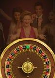 Ruletowy koło i ludzie ma zabawę w tle zdjęcie stock