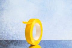 Rulla det gula elektriska bandet på en grå bakgrund royaltyfri foto