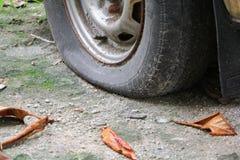 rulla det plana gummihjulet av bilen som är gammal och som är sprucken på vägen Arkivfoto
