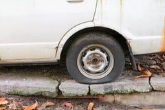 rulla det plana gummihjulet av bilen som är gammal och som är sprucken på vägen Fotografering för Bildbyråer