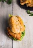 Rulla med stekte schnitzel- och salladsidor på gammal träbakgrund, tysk mat Fotografering för Bildbyråer