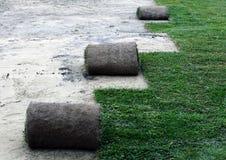 Rulla ut gräsmark för en ny gräsmatta med spridarehuvudet Royaltyfri Fotografi