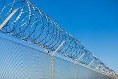 Rullad ihop rakknivtråd överst av ett staket royaltyfri bild