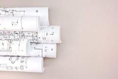 Rullande arkitektoniska ritningar och konstruktionsplan på skrivbordet royaltyfri bild