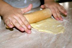 Rullande deg för liten flicka i köket arkivfoton