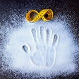 Rullande gul måttband och handprint på det spridda sockret arkivbild