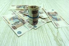 Rullande in i ett rör och bundet med sedlar för en gummibandryss på pengarbakgrund royaltyfri fotografi