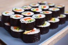 Rullande Maki sushi med laxen, gräslöken och avokadot på en grå platta arkivbild