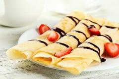 Rullande pannkakor med jordgubben på plattan på vit träbakgrund Royaltyfri Foto