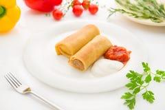 Rullande pannkakor som är välfyllda med kött på den vita plattan Royaltyfria Bilder