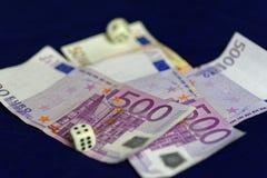 Rullande tärning på femhundra eurosedlar Arkivbild