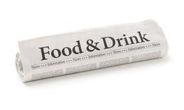 Rullande tidning med den rubrikmaten och drinken Arkivfoto