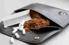 Rullande tobak i en lädersvartpåse med rullande papper och filter Royaltyfri Foto
