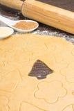 Rullande ut ljust rödbrun bröddeg med klippformer av julgarnering Arkivbild