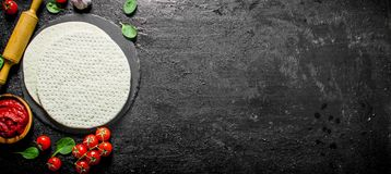 Rullande ut pizzadeg med den tomatdeg, spenat och körsbäret arkivfoto