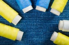 Rullar av blåa, vita och gula trådar ordnade i en halvcirkel på grov bomullstvill med kopieringsutrymme royaltyfri foto