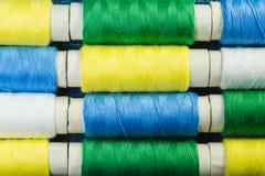 Rullar av den blåa, gula, gröna och vita sy tråden som ordnas i rader på grov bomullstvill royaltyfri foto