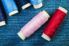 Rullar av den blåa, rosa och röda sy tråden på grov bomullstvill fotografering för bildbyråer