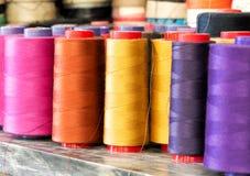 Rullar av den färgrika bomullstråden på metallhylla Royaltyfri Foto
