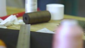Rullar av trådar och knappar på den gamla trätabellen stock video