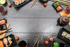 Rullar den fastställda sashimien för sushi och sushi omkring mörk bakgrund Royaltyfri Fotografi
