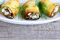 Rullar för zucchini för ostmassaost Den grillade zucchinin rullar med ostmassaost och dill på en platta och en trätabell Royaltyfria Foton