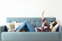 Rullar med ögonen bärande virtuell verklighet för den attraktiva kvinnan att ligga på en soffa Livsstilvirtuell verklighetbegrepp arkivbilder