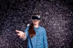 Rullar med ögonen bärande virtuell verklighet för den härliga kvinnan mot stor blac Royaltyfri Bild