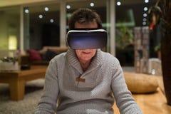 Rullar med ögonen bärande virtuell verklighet för den höga mannen hemma Royaltyfri Fotografi