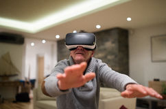 Rullar med ögonen bärande virtuell verklighet för den höga mannen hemma Royaltyfria Foton
