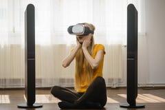 Rullar med ögonen bärande virtuell verklighet för flickan hemma Arkivfoton