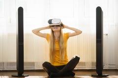 Rullar med ögonen bärande virtuell verklighet för flickan hemma Fotografering för Bildbyråer