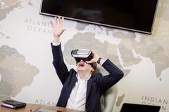 Rullar med ögonen bärande virtuell verklighet för mannen, affärsmandanandegester Arkivbild