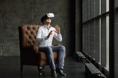 Rullar med ögonen bärande virtuell verklighet för mannen hållande ögonen på filmer eller spelavideospel Vrhörlurar med mikrofonde Arkivbilder