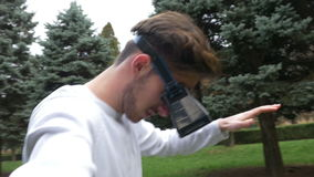 Rullar med ögonen bärande virtuell verklighet för mannen i verkligt direkt i parkerar flyttning och växelverkan med den faktiska  stock video