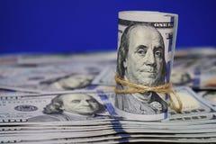 Rulle av amerikanska dollar en bakgrund av spritt hundra dollarräkningar royaltyfria bilder