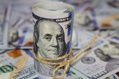 Rulle av amerikanska dollar en bakgrund av spritt hundra dollarräkningar royaltyfri foto