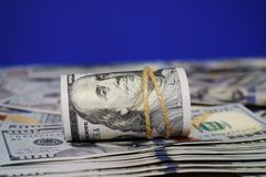 Rulle av amerikanska dollar en bakgrund av spritt hundra dollarräkningar arkivbilder