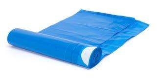 Rulle av blåa plast- avskrädepåsar som isoleras på vit Royaltyfri Fotografi